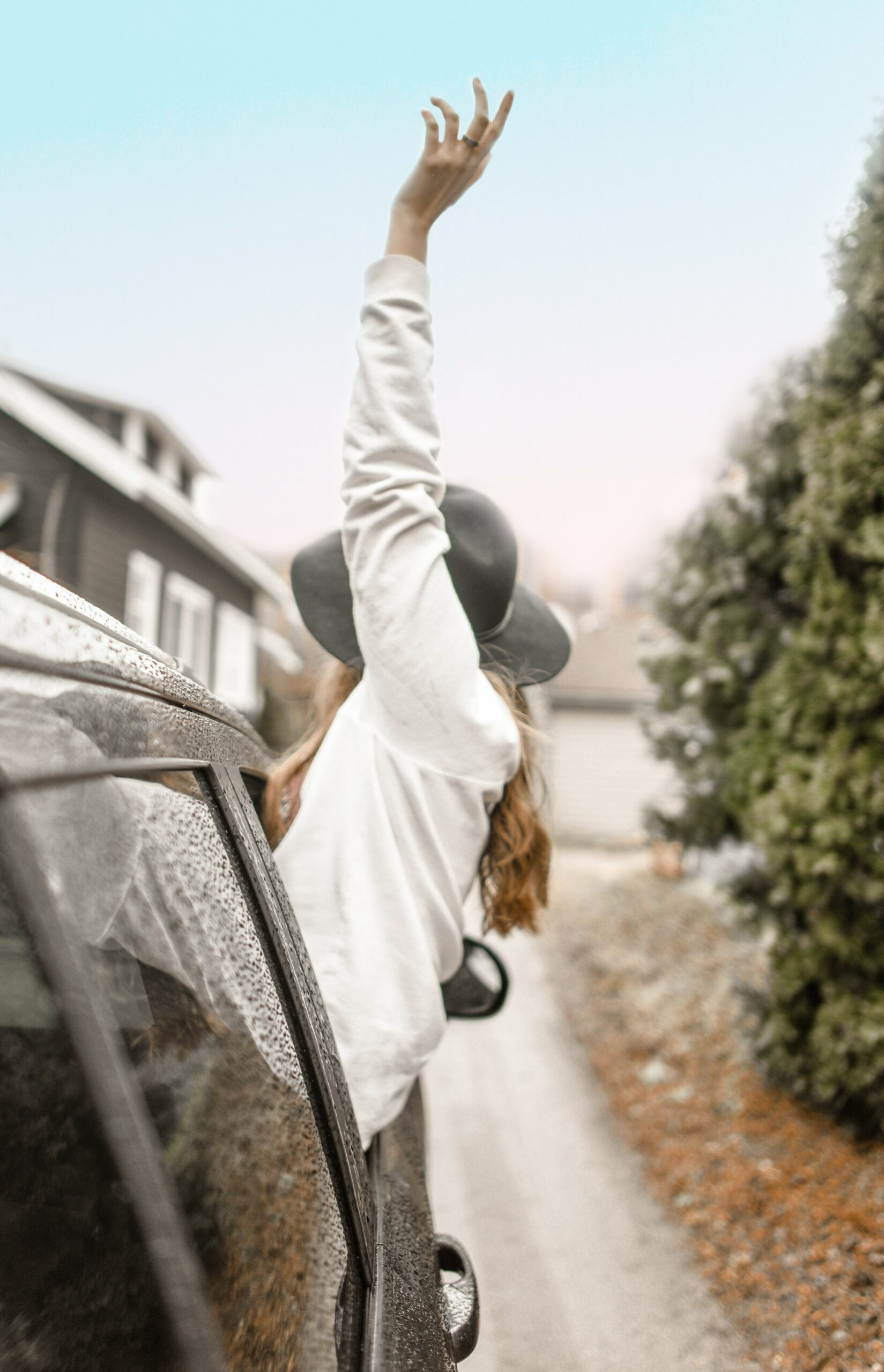 Raising hand out of window of car