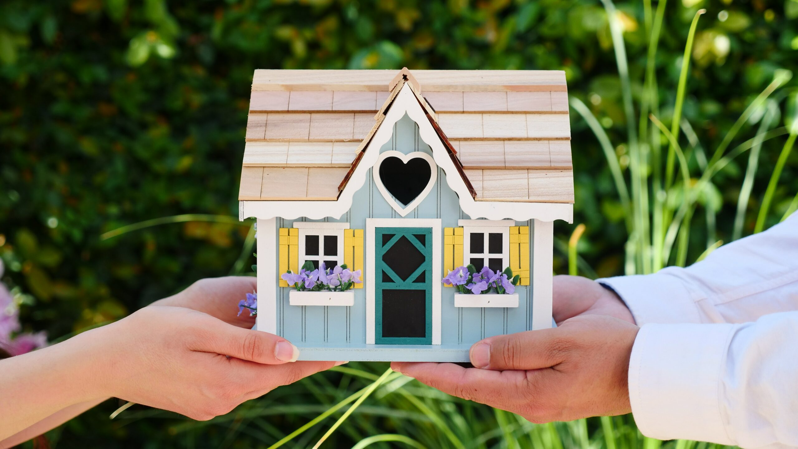 Photo of couple holding a doll house