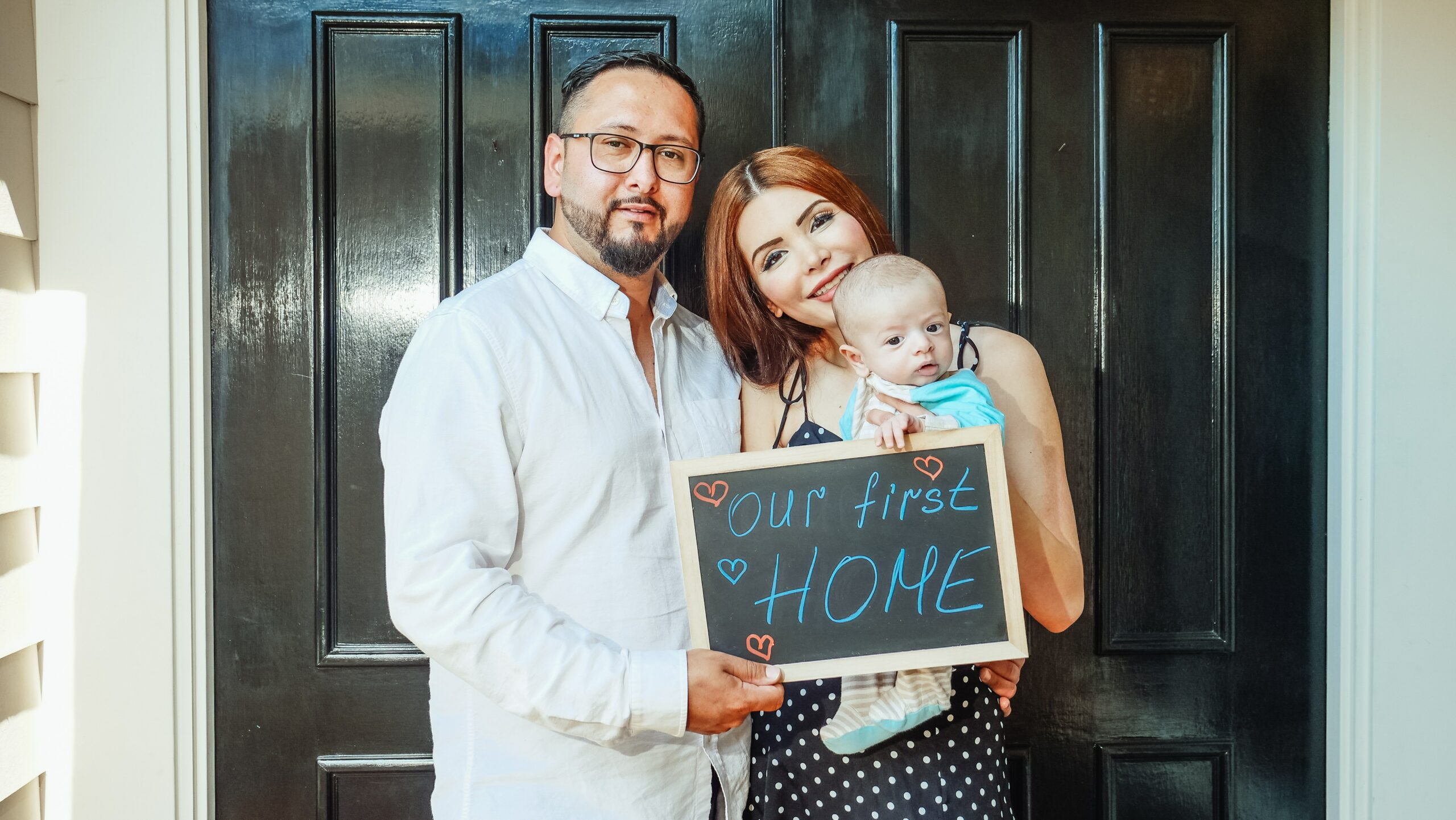 our first home family in front of door holding sign